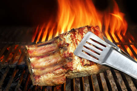 charred: Big Chop Of Pork Ribs On The Hot BBQ Grill With Flames On The Black Background. Cookout Scene Stock Photo