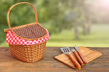 Close-up Of Picnic Banch With Hamper And BBQ Grill Tools And Summer Garden With Sunbeams In The Background