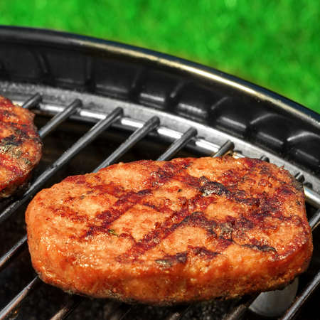 hamburger: Close-up Of BBQ Hamburger Patties On The Hot Portable Charcoal Grill. Backyard Grass In The Background. Cookout Food For Summer Weekend Picnic Or Party.