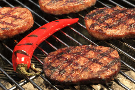 lawn party: Close-up Of BBQ Hamburger Patties And Chili Pepper On The Hot Charcoal Grill. Vibrant Backyard Lawn In The Background. Cookout Food For Summer Weekend Picnic Or Party. Stock Photo