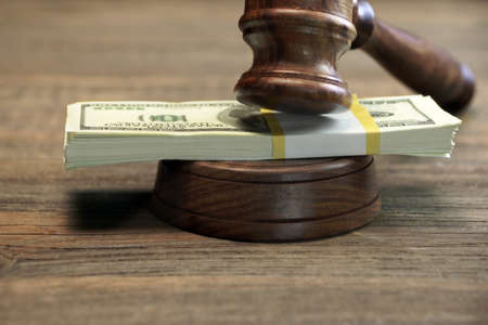 bail: Concept For Corruption, Bankruptcy Court, Bail, Crime, Bribing, Fraud, Auction Bidding. Judges or Auctioneer Gavel, Soundboard And Bundle Of Dollar Cash On The Rough Wooden Textured Table Background.