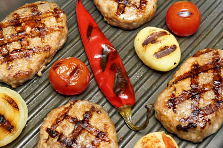 cook griddle: Close-up of hot homemade pan-fried burgers, potato, tomato and chili pepper in the grill-pan. Top View Stock Photo