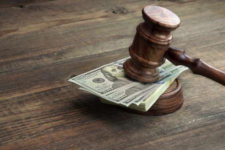 ピカピカに磨かれた小槌、響板、大まかな木製テーブルの上のドルの現金の束を判断します。概念の破損、破産裁判所、保釈、ビジネス、金融犯罪