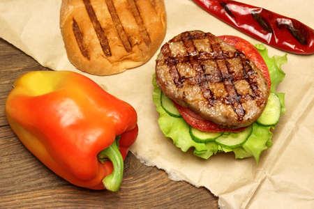grill chicken: Close-up Top View Of Grilled Hamburger On The Brown Paper, Old Rough Wooden Rustic Table In The Background.