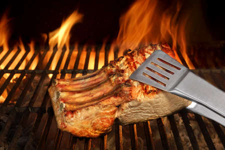 cook out: Big Chop Of Pork Ribs On The Hot BBQ Grill With Flames On The Black Background. Cookout Scene Stock Photo