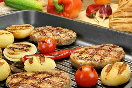 cook griddle: Homemade pan-fried burgers, pepper and grilled potato balls in the hot grill-pan on rustic dinning table. Hamburgers Ingredients in the background. Rustic Food Still-life