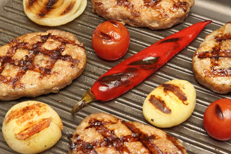 griddle: Close-up of hot homemade pan-fried burgers, potato, tomato and chili pepper in the grill-pan. Top View Stock Photo
