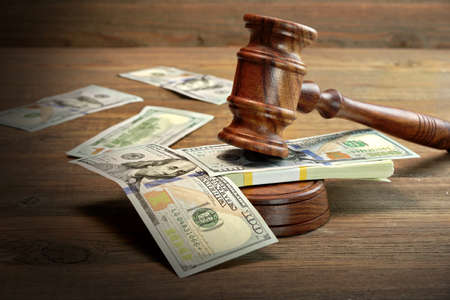 부패, 파산 법원, 보석, 범죄, 뇌물, 사기, 경매 입찰에 대 한 개념입니다. 심사 위원 또는 거친 나무 질감 표 배경에 경매 디노, 사운드 보드와 달러 현