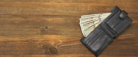 wealth concept: High Angle View Of Modern Black leather Mens Wallet With Dollar Cash On The Old Rough Wood Textured Background With Copy Space