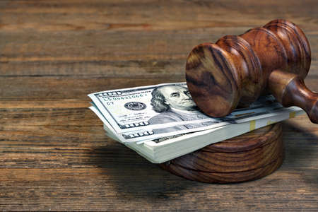 Close-up Of Judges Gavel, Soundboard And Bundle Of Dollar Cash On The Rough Wooden Table. Concept For Corruption, Bankruptcy Court, Bail, Business Or Financial Crime, Bribing, Fraud, Auction Bidding Stock Photo