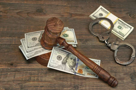 Dollars Cash, Real Handcuffs And Judge Gavel On Rough Wood Background. Concept For Arrest, Corruption, Bail, Crime, Bribing or Fraud.
