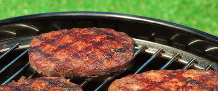 cook out: Close-up Of BBQ Hamburger Patties On The Hot Portable Charcoal Grill. Backyard Grass In The Background. Cookout Food For Summer Weekend Picnic Or Party.