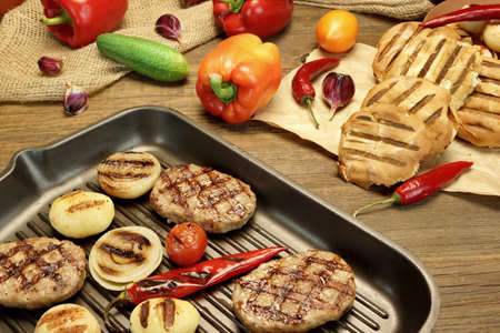 grilled potato: Homemade pan-fried burgers, pepper and grilled potato balls in the hot grill-pan on rustic dinning table. Hamburgers Ingredients in the background. Rustic Food Still-life