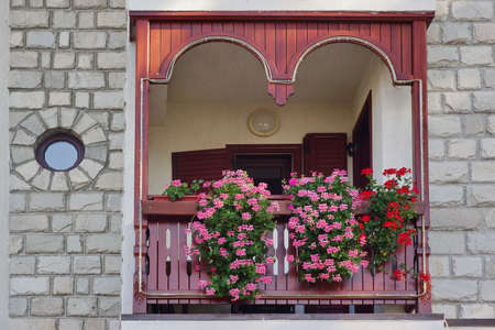 decorative balcony: Decorative Home Balcony Garden With Petunia In The Basket Hanging On The Wood Railing