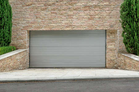 garage on house: Automatic Electric Roll-up Commercial Garage Gate Or Push-up Door In The Modern Building Ground Floor Stock Photo