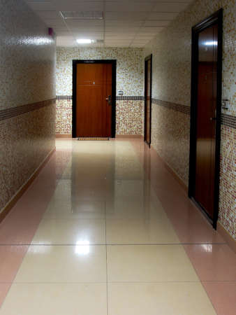 multifamily: Long Dark Corridor With Metal Doors, Tilled Wall And Floor In The Residential Building Stock Photo