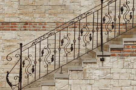 stone stairs: Modern Vintage Style Straight Stone Staircase With Black Wrought Iron Ornate Handrail  Near Tiled Stonewall, Architecture Background