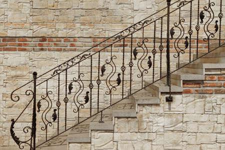 Modern Vintage Style Straight Stone trap met zwarte smeedijzeren Sierlijke Leuning Dichtbij Tegels Stonewall, Architectuur Achtergrond Stockfoto