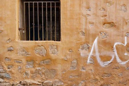 rejas de hierro: Pared de piedra vieja del edificio amarillo con ventana y barras oxidadas, Fondo
