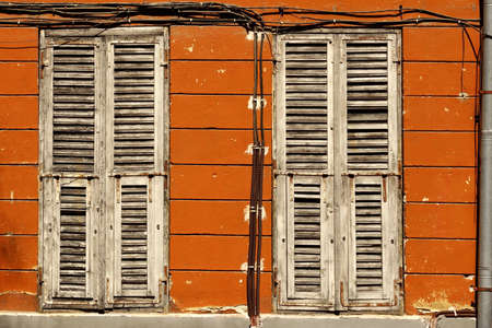 old building facade: Two Dirty Wooden Closed Shutters In The Old Building Facade Wall  With Many Electric Wires And Rainwater Pipe