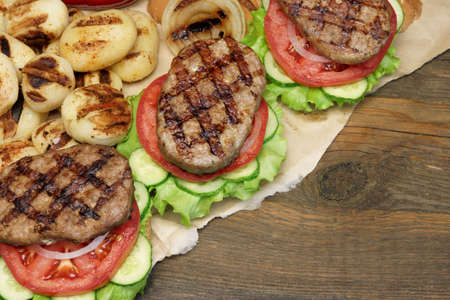 bbq grill: Picnic Lunch With Homemade BBQ Grilled Burgers And Fried Potatoes On The Rustic Table Background Top View Stock Photo