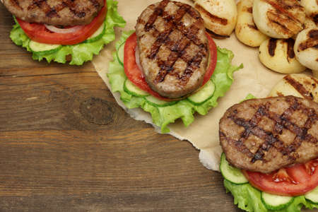 cook out: Picnic Table Top With BBQ Grilled Burgers And Vegetables, Outdoor Dinner Concept, Overhead View Stock Photo