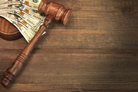 bribing: Concept For Corruption, Bankruptcy Court, Bail, Crime, Bribing, Fraud, Auction Bidding. Judges or Auctioneer Gavel, Soundboard And Bundle Of Dollar Cash On The Rough Wooden Textured Table Background.