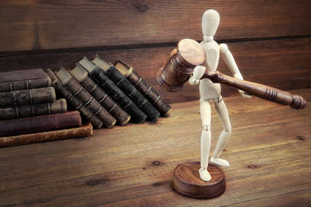 advocate: Wooden Figurine With Judges Gavel  And Old Law Book On The Rough Wood Table Background