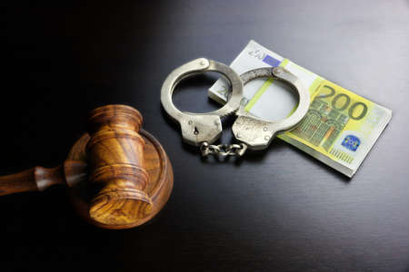 euro: Concept For Corruption, Bankruptcy, Bail, Crime, Bribing, Fraud. Judges Gavel, Handcuffs   And Euro Cash On The Rough Black Wooden Textured Table Background. Stock Photo