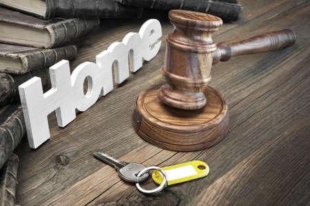 記号の家、ドアの鍵、裁判官または競売小槌、木製テーブルの上の古い法律本。破産、裁判のためコンセプト税、住宅ローン、オークションの入札