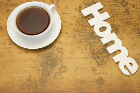 town house: Dream Or Miss Of Own Home Concept. White Tea Cup And Wooden Sign HOME On The Old World Map Background. Overhead View. Stock Photo