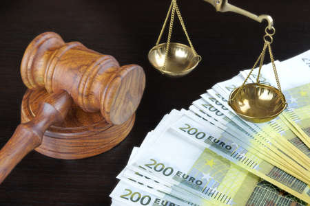 bribing: Concept For Corruption, Bankruptcy, Bail, Crime, Bribing, Fraud. Judges Gavel, Scale Of Justice And Euro Cash On The Rough Black Wooden Textured Table Background. Stock Photo