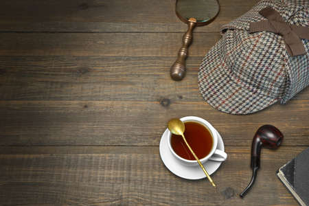 sleuth: Sherlock Holmes Concept. Private Detective Tools On The Wood Table Background. Deerstalker Cap,  Magnifier, Key, Cup, Notebook, Smoking Pipe. Stock Photo