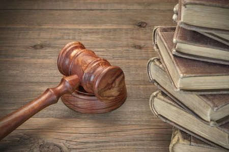 statute: Wooden Judges Gavel And Old Law Books On The Rough Wooden Table In The Background. Law Concept. Top View