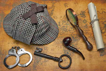 old items: Overhead View Of Sherlock Holmes Deerstalker Hat  And Private Detective Tools On The Old World Map Background. Items Include Vintage Magnifying Glass, Retro Key, Manuscript, Smoking Pipe,  And Handcuffs