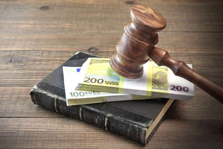 seizure: Concept For Corruption, Bankruptcy Court, Bail, Crime, Bribing, Fraud, Auction Bidding. Judges or Auctioneer Gavel And Bundle Of Euro Cash On The Rough Wooden Textured Table Background. Top View