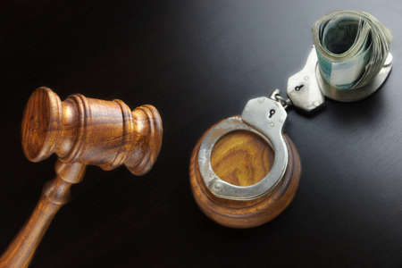 bail: Concept For Corruption, Bankruptcy, Bail, Crime, Bribing, Fraud. Judges Gavel, Handcuffs   And Russian Cash On The Rough Black Wooden Textured Table Background.