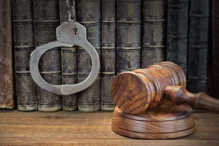 Real Handcuffs, Wooden Judge Gavel And Old Law Books On The Rough Brown Wooden Table Background. Arrest in the Courtroom Concept Or Release From Custody Archivio Fotografico