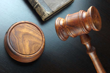 Judges  Or Auctioneers Walnut Gavel And Old Law Book  On The Black Wooden Table Background In The Back Light. Overhead View. Lawsuit or Auction Bidding Concept