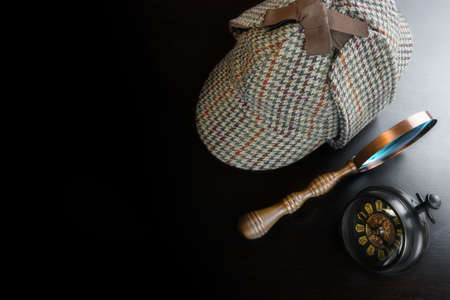 Sherlock Holmes Deerstalker Hat And Vintage Clock And   Magnifying Glass On The Black Wooden Table Background. Overhead View.  Investigation Concept. Stock Photo