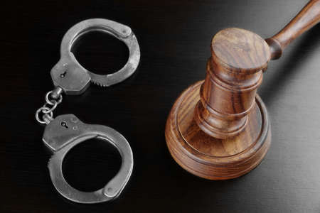 back light: Real Judges Gavel, Sound Block  And Handcuffs On The Empty Black Table In The Back Light. Overhead View. Stock Photo