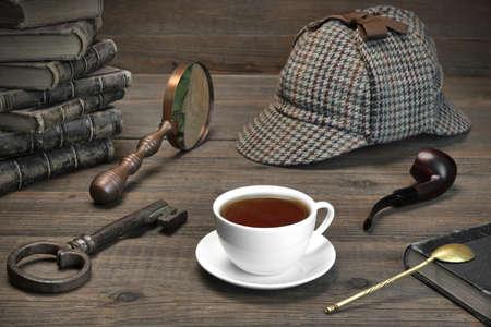 셜록 홈즈 개념입니다. 우드 테이블 배경에 사립 탐정 도구. 사슴 사냥꾼 모자, 돋보기, 키, 컵, 노트북, 흡연 파이프.