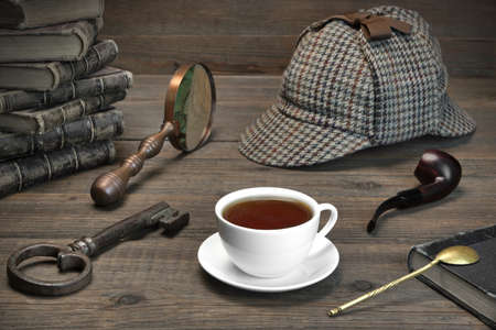 holmes: Sherlock Holmes Concept. Private Detective Tools On The Wood Table Background. Deerstalker Cap,  Magnifier, Key, Cup, Notebook, Smoking Pipe. Stock Photo