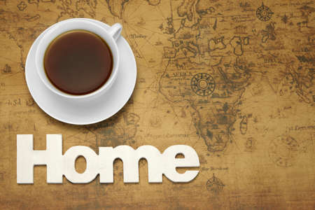 tea house: Dream Or Miss Of Own Home Concept. White Tea Cup And Wooden Sign HOME On The Old World Map Background. Overhead View. Stock Photo