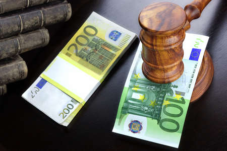 bidding: Concept For Corruption, Bankruptcy, Bail, Crime, Bribing, Fraud, Auction Bidding. Judges or Auctioneer Gavel, Soundboard And Euro Cash On The Rough Black Wooden Textured Table Background. Stock Photo