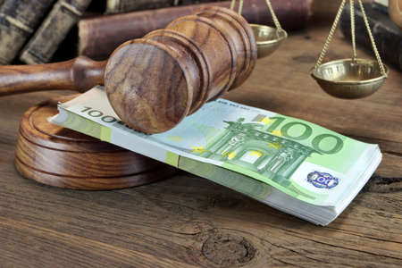 auctioneer: Concept For Corruption, Bankruptcy Court, Bail, Crime, Bribing, Fraud.  Judges or Auctioneer Gavel And Bundle Of Euro Cash On The Rough Wooden Table. Top View Stock Photo