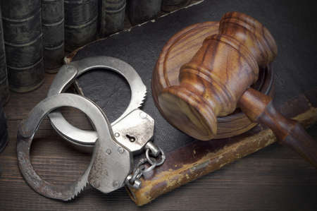 restraints: Real Handcuffs, Wooden Judge Gavel And Old Law Books On The Rough Brown Wooden Table Background. Arrest in the Courtroom Concept Or Release From Custody Stock Photo