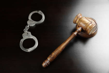 derecho penal: Real jueces martillo, bloque de los sonidos y las esposas En La Tabla Vac�o Negro En La luz de fondo. Vista desde arriba.