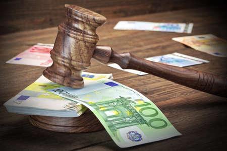 Konzept für Korruption, Bankrott, Bail, Verbrechen, Bestechen, Betrug, Auktion Richter oder Versteigerer Hammer, Soundboard, Bündel von Euro-Bargeld und alte Gesetz Buch-Bibliothek auf der rauen Holztisch Hintergrund.