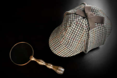 sherlock: Sherlock Holmes Deerstalker Hat And Vintage  Magnifying Glass On The Black Wooden Table Background. Overhead View.  Investigation Concept.